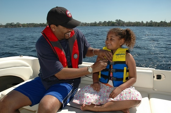 father putting life jacket on daughter